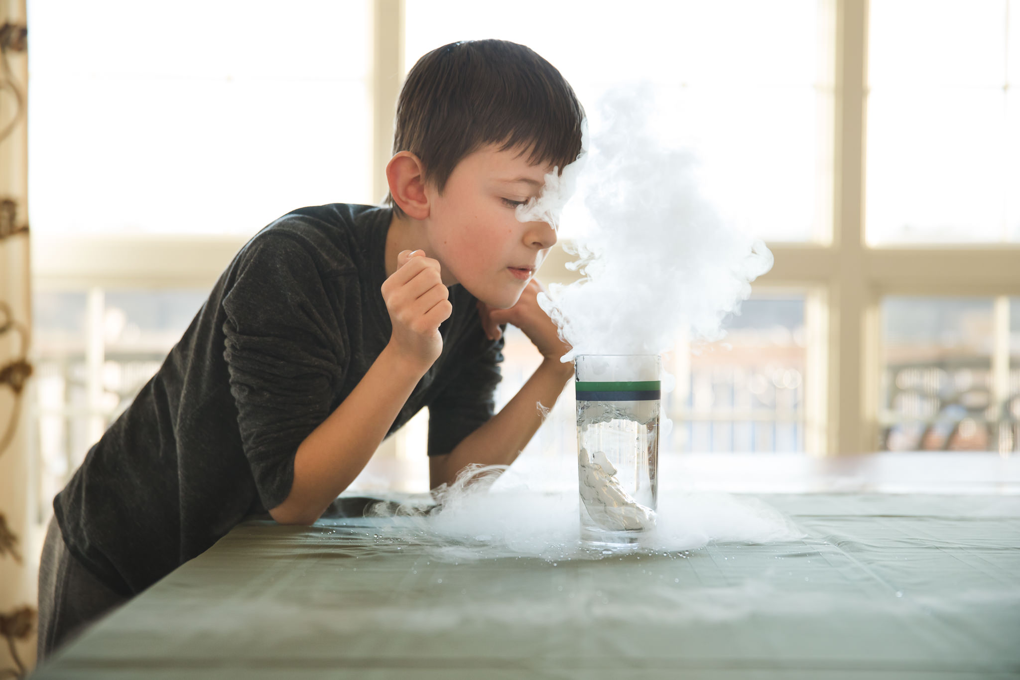 Boy blowing dry ice cloud.