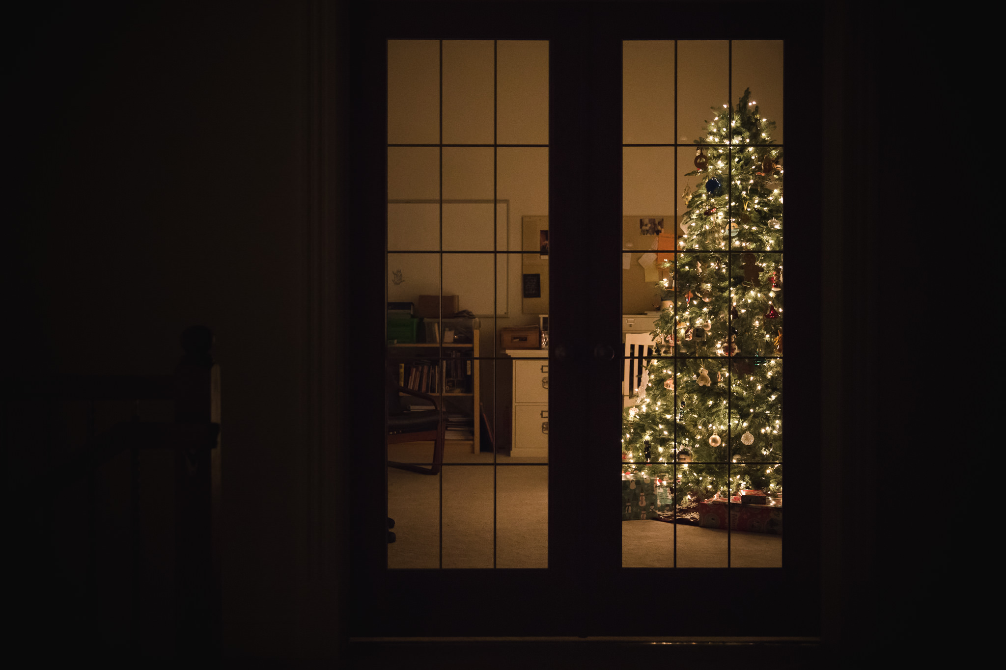 Christmas tree in den behind french doors