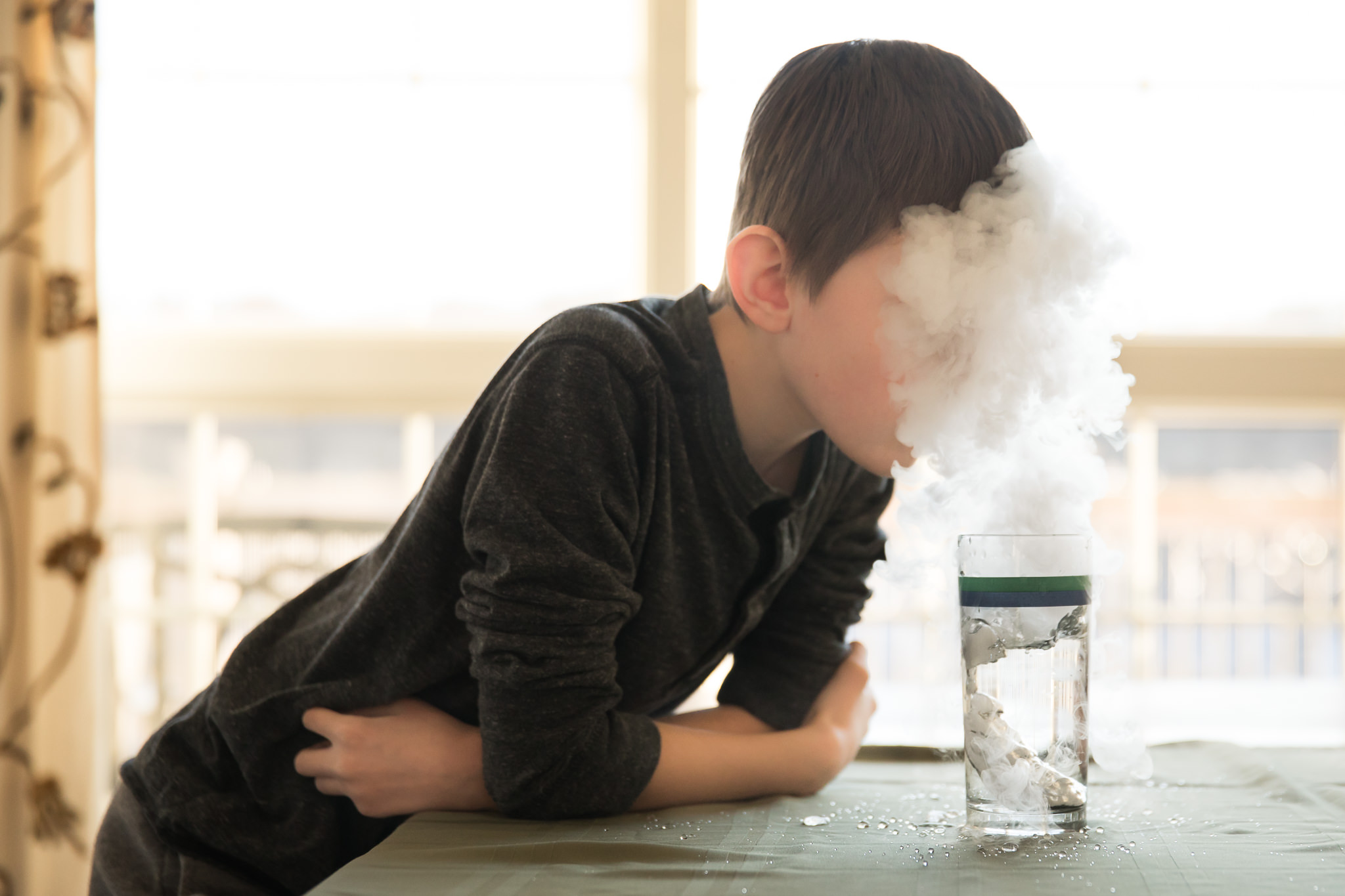 Boy with a face hidden by dry ice vapor.